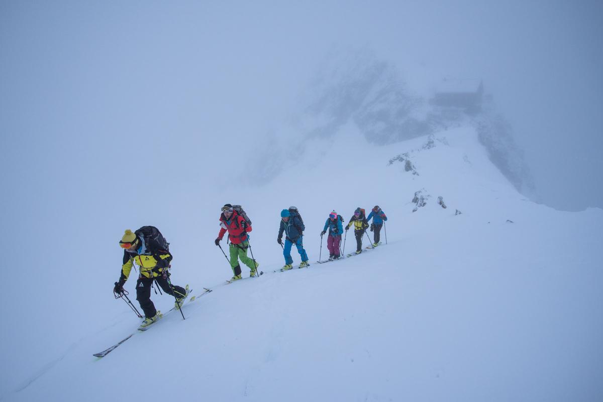 Simon guide l'équipe Suisse, la cabane des Vignettes s'éloigne déjà dans le brouillard en fond.